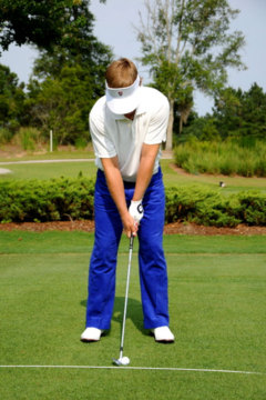 At address, the head should be positioned between the feet whether you are hitting a driver or an iron.