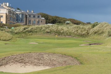 The 18th green of Portmarnock Links sits in the shadow of some dunes and the old Jameson house that's now a hotel.