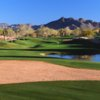 A view of green with water coming into play and mountains in background at Tatum Ranch Golf Club