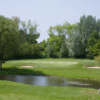 A view over the pond of green flanked by sand traps at Mill Hill Golf Club