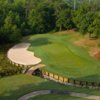 A view of a green protected by a bunker at Rock Creek Golf Club