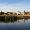View of a green over water at Peoria Pines Golf Club